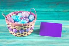 Ιώδη και μπλε αυγά Πάσχας σε ένα καλάθι με μια κάρτα μπλε ξύλινος ανασκόπησης Πάσχα ευτυχές Στοκ Φωτογραφία
