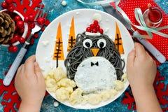Ιδέα τέχνης τροφίμων διασκέδασης για τα παιδιά - penguin μαύρο spagehetti με τηγανισμένος Στοκ Εικόνα