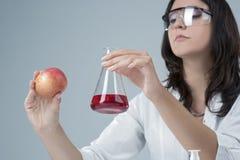 Ιδέες ιατρικής και έρευνας Εργαστηριακό γυναικείο προσωπικό που εξετάζει το δείγμα της Apple και το υγρό δοκιμής στη φιάλη Στοκ φωτογραφία με δικαίωμα ελεύθερης χρήσης