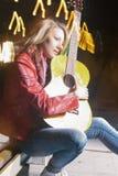 Ιδέες και έννοιες τρόπου ζωής νεολαίας Καυκάσια ξανθή γυναίκα που παίζει την κιθάρα υπαίθρια τη νύχτα Στοκ Φωτογραφίες