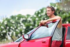Ιδιοκτήτης αυτοκινήτων - νεαρός άνδρας και νέο κόκκινο αυτοκίνητο έξω Στοκ εικόνες με δικαίωμα ελεύθερης χρήσης