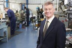 Ιδιοκτήτης του εργοστασίου εφαρμοσμένης μηχανικής με το προσωπικό στο υπόβαθρο Στοκ Φωτογραφία