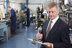 Ιδιοκτήτης του εργοστασίου εφαρμοσμένης μηχανικής με το προσωπικό στο υπόβαθρο Στοκ Εικόνες