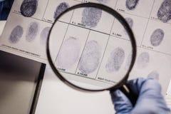 Ιδιωτικός αστυνομικός μέσω μιας ενίσχυσης - γυαλί που εξετάζει ένα δακτυλικό αποτύπωμα Στοκ φωτογραφία με δικαίωμα ελεύθερης χρήσης