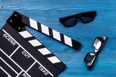 Ιδιότητες του σκηνοθέτη Κινηματογράφος clapperboard και γυαλιά ηλίου στην μπλε ξύλινη τοπ άποψη επιτραπέζιου υποβάθρου στοκ εικόνα