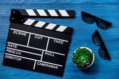 Ιδιότητες του σκηνοθέτη Κινηματογράφος clapperboard και γυαλιά ηλίου στην μπλε ξύλινη τοπ άποψη επιτραπέζιου υποβάθρου στοκ φωτογραφία