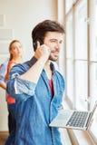 Ιδρυτής με το lap-top που καλεί το τηλέφωνο Στοκ Φωτογραφία