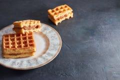 Κάθετες γλυκές φρέσκες βιενέζικες βάφλες άποψης σε ένα πιάτο σε έναν μαύρο πίνακα διάστημα αντιγράφων Ευρωπαϊκά για το πρόγευμα στοκ φωτογραφία με δικαίωμα ελεύθερης χρήσης