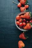 Κάθετες φρέσκες κεράσια και φράουλες φωτογραφιών στο μαύρο ξύλο Στοκ Φωτογραφίες