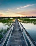 Κάθετη άποψη ενός όμορφου ηλιοβασιλέματος πέρα από τα παράκτια νερά με μια πολύ μακριά ξύλινη αποβάθρα θαλασσίων περίπατων στο κέ στοκ εικόνα