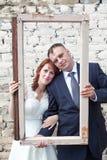 Κάθετη εικόνα της νύφης και του νεόνυμφου που κοιτάζουν μέσω του πλαισίου πορτρέτου Στοκ φωτογραφία με δικαίωμα ελεύθερης χρήσης