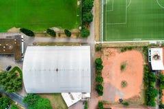 Κάθετη εναέρια άποψη μιας αίθουσας αντισφαίρισης δίπλα σε μια πράσινη πίσσα ποδοσφαίρου με τη χλόη μπροστά από έναν κόκκινο τομέα στοκ εικόνα