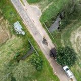 Κάθετη εναέρια άποψη του περάσματος ενός ρεύματος κάτω από μια στενή οδό με ένα καλώδιο τροφοδοσίας επάνω από το Στοκ Εικόνες