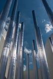 Κάθετη ομάδα μεταλλικών σωλήνα και μπλε ουρανού χάλυβα στο υπόβαθρο Στοκ Φωτογραφίες