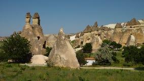 Κάθετοι κωνικοί σχηματισμοί βράχου με ένα άσπρο κτήριο φιλμ μικρού μήκους