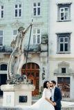 Κάθετο γαμήλιο πορτρέτο του όμορφου νεόνυμφου που φιλά μαλακά την πανέμορφη νύφη στο μάγουλο καθμένος στον παλαιό στοκ εικόνα