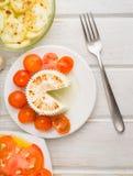 Κάθετο κομμάτι άποψης του μαλακού τυριού με τις ντομάτες κερασιών στο woode Στοκ εικόνα με δικαίωμα ελεύθερης χρήσης