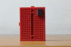 Κάθετο κόκκινο protoboard με ένα τσιπ ολοκληρωμένου κυκλώματος στοκ εικόνες με δικαίωμα ελεύθερης χρήσης