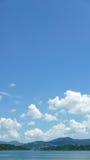 Κάθετο πράσινο βουνό, λίμνη, μπλε ουρανός, άσπρο σύννεφο Στοκ Εικόνα