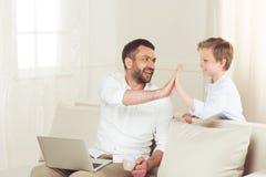 Κάθισμα με το lap-top και δόσιμο υψηλών πέντε στο μικρό γιο του στο σπίτι Στοκ Εικόνες