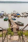 Κάθοδος στην ξύλινες γέφυρα και τις μικρές βάρκες και motorboats χώρων στάθμευσης στον ποταμό Βόλγας στοκ εικόνες