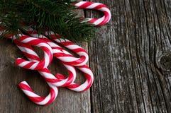Κάλαμοι καραμελών Χριστουγέννων στον παλαιό ξύλινο πίνακα με τον κλάδο έλατου Στοκ Φωτογραφίες