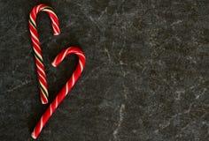 Κάλαμος καραμελών σε ένα μαύρο μαρμάρινο υπόβαθρο αφηρημένο ανασκόπησης Χριστουγέννων σκοτεινό διακοσμήσεων σχεδίου λευκό αστεριώ στοκ εικόνες