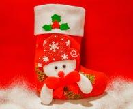 Κάλτσα και χιόνι Χριστουγέννων σε ένα κόκκινο υπόβαθρο στοκ εικόνες με δικαίωμα ελεύθερης χρήσης
