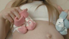 Κάλτσες για το μελλοντικό νεογέννητο αγοράκι ή το κορίτσι στη γυμνή κοιλιά μιας εγκύου γυναίκας φιλμ μικρού μήκους