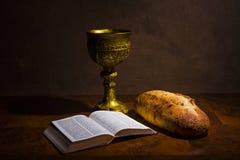 Κάλυκας με το ψωμί κρασιού και ιερή Βίβλος σε έναν πίνακα στοκ εικόνες