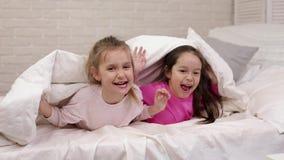 Κάλυψη δύο χαριτωμένη μικρή κοριτσιών παιδιών με το κάλυμμα απόθεμα βίντεο