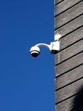 Κάμερα ασφαλείας καλυμμένο στον ασβεστοκονίαμα τοίχο ενάντια στο βαθύ μπλε ουρανό Στοκ φωτογραφία με δικαίωμα ελεύθερης χρήσης