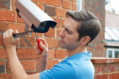 Κάμερα ασφαλείας συναρμολογήσεων ατόμων στον τοίχο σπιτιών Στοκ Φωτογραφίες