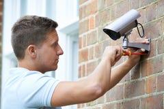 Κάμερα ασφαλείας συναρμολογήσεων συμβούλων ασφαλείας στον τοίχο σπιτιών Στοκ Φωτογραφίες