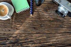 Κάμερα, γυαλιά και σημειωματάριο στο ξύλο, επάνω από την άποψη στοκ φωτογραφίες