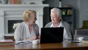 Κάμερα Ιστού, ηλικιωμένο ζεύγος που έχει τη διασκέδαση στην επικοινωνία με την οικογένεια στο διαδίκτυο στο άνετο καθιστικό απόθεμα βίντεο