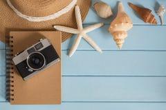 Κάμερα και κοχύλια στο ξύλινο πάτωμα του μπλε Στοκ φωτογραφία με δικαίωμα ελεύθερης χρήσης