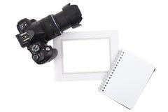Κάμερα και πλαίσιο με το σημειωματάριο στοκ φωτογραφίες