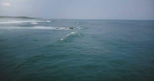 Κάμερα κηφήνων που γυρίζει αριστερά μετά από το μεγάλο ωκεάνιο κύμα που φθάνει στην ακτή, που αφρίζει και που συντρίβει σε μια νε απόθεμα βίντεο