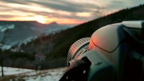 Κάμερα κινηματογραφήσεων σε πρώτο πλάνο που τίθεται ως στόχος να πιάσει το ηλιοβασίλεμα Χειμερινά τοπία, πορτοκαλής ουρανός και η στοκ φωτογραφίες