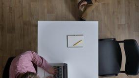 Κάμερα που κινείται πέρα από τους επιχειρηματίες που εργάζονται και που κάθονται στον πίνακα στο σύγχρονο γραφείο, topshot φιλμ μικρού μήκους