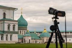Κάμερα σε ένα τρίποδο ενάντια στο σκηνικό της αρχιτεκτονικής Στοκ Εικόνες