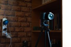 Κάμερα στο τρίποδο στο δωμάτιο με το ράφι στοκ φωτογραφία με δικαίωμα ελεύθερης χρήσης