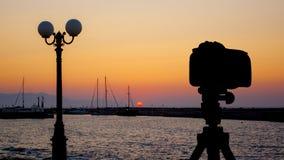 Κάμερα στο τρίποδο με τη θάλασσα και ηλιοβασίλεμα στο υπόβαθρο στοκ φωτογραφία με δικαίωμα ελεύθερης χρήσης