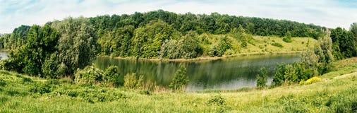 Κάμψη του ποταμού με τα πράσινα δέντρα και της χλόης στην ακτή στοκ εικόνα