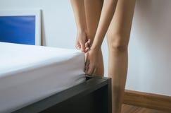 Κάνετε ένα κρεβάτι, γυναίκα που κάνει το κρεβάτι της στο δωμάτιο μετά από ξυπνήστε στοκ φωτογραφία