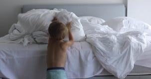 Κάνετε ένα κρεβάτι, παιδί που κάνει το κρεβάτι της στο δωμάτιο μετά από ξυπνήστε απόθεμα βίντεο