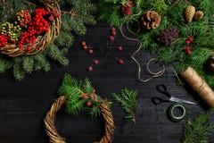 Κάνετε ένα στεφάνι Χριστουγέννων με τα χέρια σας Κομψός κλάδος, στεφάνι Χριστουγέννων και δώρα σε ένα μαύρο ξύλινο υπόβαθρο Στοκ φωτογραφίες με δικαίωμα ελεύθερης χρήσης