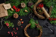 Κάνετε ένα στεφάνι Χριστουγέννων με τα χέρια σας Κομψός κλάδος, στεφάνι Χριστουγέννων και δώρα σε ένα μαύρο ξύλινο υπόβαθρο Στοκ Εικόνα