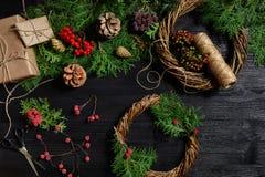 Κάνετε ένα στεφάνι Χριστουγέννων με τα χέρια σας Κομψός κλάδος, στεφάνι Χριστουγέννων και δώρα σε ένα μαύρο ξύλινο υπόβαθρο Στοκ εικόνα με δικαίωμα ελεύθερης χρήσης